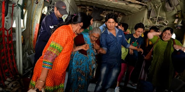 Indian Air Force (IAF) personnel assist an elderly Indian woman, as she disembarks from an IAF aircraft on arrival from Nepal, at Palam Air Force Station near New Delhi on April 28, 2015, after she and others were transported from the earthquake stricken Himalayan nation.  Hungry and desperate villagers rushed towards relief helicopters in remote areas of Nepal, begging to be airlifted to safety, four days after a monster earthquake killed more than 5,000 people. AFP PHOTO/Chandan KHANNA        (Photo credit should read Chandan Khanna/AFP/Getty Images)