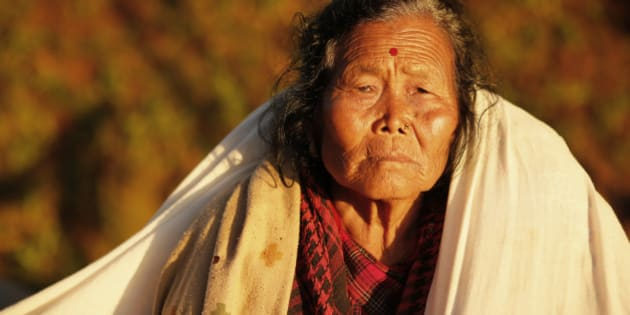 An elderly villager sit in the evening sun with a blanket in the destroyed village of Paslang near the epicenter of Saturday's massive earthquake in the Gorkha District of Nepal, Tuesday, April 28, 2015.  Military operations continue Tuesday to reach the isolated areas following the powerful earthquake that has devastated the nation and killed at least 4,400 people, according to district official Surya Mohan Adhikari. (AP Photo/Wally Santana)