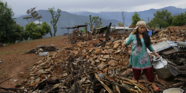 A woman recovers cooking pots from her collapsed home destroyed village of Paslang near the epicenter of Saturday's massive earthquake in the Gorkha District of Nepal, Tuesday, April 28, 2015.  Military operations continue Tuesday to reach the isolated areas following the powerful earthquake that has devastated the nation and killed at least 4,400 people, according to district official Surya Mohan Adhikari. (AP Photo/Wally Santana)
