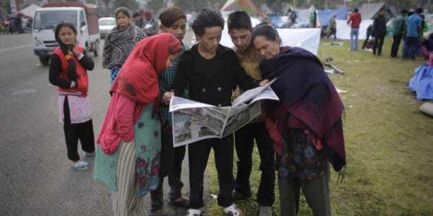 Survivors of Saturday's earthquake read the newspaper at a makeshift camp in Kathmandu, Nepal, Tuesday, April 28, 2015. A strong earthquake shook Nepal's capital and the densely populated Kathmandu valley on Saturday. (AP Photo/Altaf Qadri)