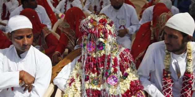An Indian groom sits decorated with flowers during a mass marriage ceremony in Ahmadabad, India, Saturday, March 21, 2015. 112 Muslim couples from impoverished families tied the knot in a single ceremony organized by a social organization. (AP Photo/Ajit Solanki)