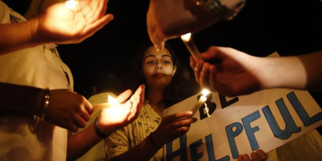 A college student participates in a candle light vigil for victims of Nepal's earthquake, in Mumbai, India, Wednesday, April 29, 2015. The 7.8 magnitude earthquake shook Nepal's capital and the densely populated Kathmandu valley on Saturday devastating the region and leaving tens of thousands shell-shocked and sleeping in streets. (AP Photo/Rajanish Kakade)