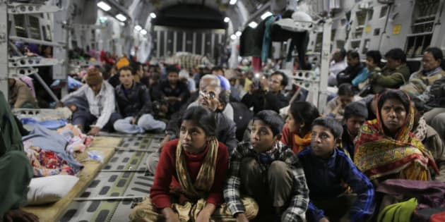 Survivors of Saturday's earthquake hold on to a cable as a military takes off with evacuees from Kathmandu to New Delhi during a midnight rescue mission by Indian Air Force, in Kathmandu, Nepal, Wednesday, April 29, 2015. (AP Photo/Altaf Qadri)
