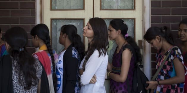 Indian students line up to buy forms for admission to the Delhi University's four-year undergraduate program in New Delhi, India, Monday, June 2, 2014. (AP Photo/Tsering Topgyal)