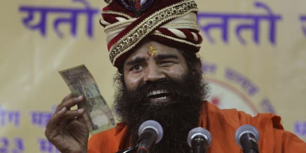 Indian yoga guru Baba Ramdev displays an Indian banknote as he makes fun of people running after money while addressing supporters in Ahmadabad, India, Monday, Feb. 3, 2014. Earlier in the day, addressing the media, Ramdev said he will launch a nationwide door-to-door campaign in support of the main opposition Bharatiya Janata Party(BJP)'s prime ministerial candidate Narendra Modi from March 1 in the run up to the 2014 parliament elections. (AP Photo/Ajit Solanki)