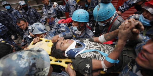 Pemba Tamang is carried on a stretcher after being rescued by Nepalese policemen and U.S. rescue workers from a building that collapsed five days ago in Kathmandu, Nepal, Thursday, April 30, 2015. Crowds cheered Thursday as a Tamang was pulled, dazed and dusty, from the wreckage of a seven-story Kathmandu building that collapsed around him five days ago when an enormous earthquake shook Nepal. (AP Photo/Niranjan Shresta)