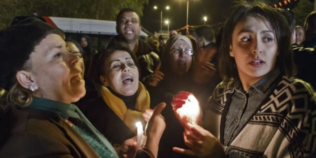 """Tunisians holding candles chant pro government slogans outside the National Bardo Museum where scores of people were killed after gunmen staged an attack, Tunis, Wednesday, March 18, 2015. Foreign tourists scrambled in panic Wednesday after militants stormed a museum in Tunisia's capital and killed scores of people, """"shooting at anything that moved,"""" a witness said. (AP Photo/Michel Euler)"""