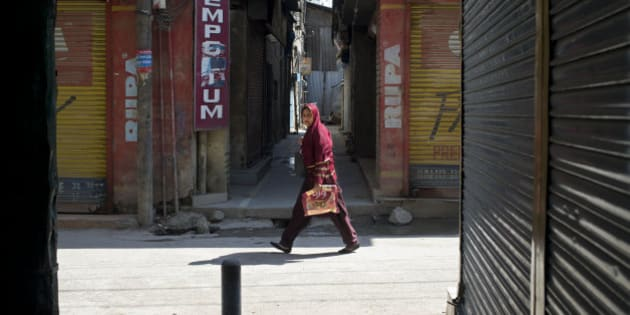 A Kashmiri Muslim woman walks past a closed market are during a strike in Srinagar, Indian controlled Kashmir, Saturday, April 11, 2015. Kashmiris closed shops and businesses in the disputed Himalayan region Saturday to protest India's plan to build townships for Hindus who fled a rebellion in Muslim-majority areas. Many of the Hindus, known as Pandits, had fled to Hindu-dominated areas in Jammu region or elsewhere in India in 1990. (AP Photo/Dar Yasin)