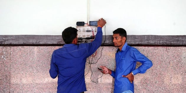 Indian passengers charge their mobile phones at Allahabad Junction in Allahabad on February 26, 2015.  India said it would spend 137 billion dollars to modernise its crumbling railways, pledging to restore the 'backbone' of the country to its former glory -- and introduce yoga lessons for stressed-out staff.   AFP PHOTO / SANJAY KANOJIA        (Photo credit should read Sanjay Kanojia/AFP/Getty Images)