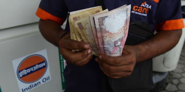 An Indian petrol pump employee counts Indian currency in Siliguri on August 28, 2013. India's rupee slumped nearly four percent to a fresh record low against the dollar as concerns about a US-led military strike against Syria compounded deepening domestic economic woes. The Indian unit, which lost three percent on August 27, was down 2.46 percent at 67.87 rupees to the dollar in afternoon trade after plunging 3.84 percent at one point to 68.74 rupee AFP PHOTO/Diptendu DUTTA        (Photo credit should read DIPTENDU DUTTA/AFP/Getty Images)