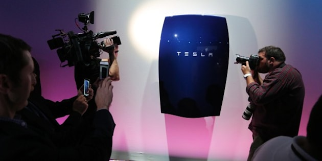 People look at newly-unveiled Tesla Powerwall batteries at the Tesla Design Studio in Hawthorne, California, April 30, 2015.  Electric car pioneer Telsa Motors unveiled a 'home battery' Thursday which its founder Elon Musk said would help change the 'entire energy infrastructure of the world.'      AFP PHOTO / David McNew        (Photo credit should read DAVID MCNEW/AFP/Getty Images)