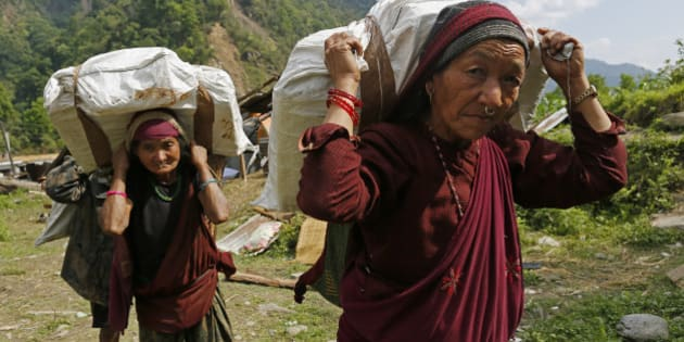 Elderly villagers start their 20km (12 mile) hike back up to their mountain home with international relief aid they received in the damaged village of Balua, near the epicenter of Saturday's massive earthquake, in the Gorkha District of Nepal, Thursday, April 30, 2015. (AP Photo/Wally Santana)