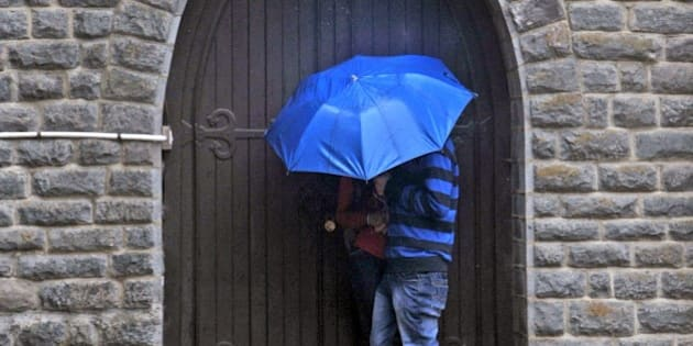 An Indian couple take shelter in a doorway of a church during heavy rainfall in Shimla on February 25, 2015. AFP PHOTO/STR        (Photo credit should read STRDEL/AFP/Getty Images)