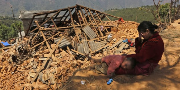 A Nepalese woman sits with her son near their house, destroyed in last week's earthquake, in Pauwathok village, Sindhupalchok district, Nepal, Saturday, May 2, 2015. Life has been slowly returning to normal in Kathmandu, but to the east, angry villagers in parts of the Sindhupalchok district said Saturday they were still waiting for aid to reach them. In the village of Pauwathok, where all but a handful of the 85 houses were destroyed, three trucks apparently carrying aid supplies roared by without stopping. (AP Photo/Manish Swarup)