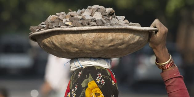 A female Indian labourer carries gravel over her head at a construction site in New Delhi on March 9, 2014. India's economy grew by a sluggish 4.7 percent in the last quarter of 2013, data showed in February, marking more bad news for the ruling Congress party ahead of looming elections. AFP PHOTO/SAJJAD HUSSAIN        (Photo credit should read SAJJAD HUSSAIN/AFP/Getty Images)