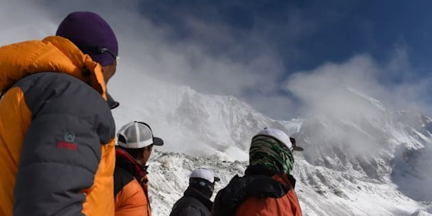 Nepalese Sherpas look up towards an area where an avalanche triggered by an earthquake occurred at Everest Base Camp on April 26, 2015, a day after the avalanche triggered by an earthquake devastated the camp. Rescuers in Nepal are searching frantically for survivors of a huge quake on April 25, that killed nearly 2,000, digging through rubble in the devastated capital Kathmandu and airlifting victims of an avalanche at Everest base Camp. The bodies of those who perished lie under orange tents. AFP PHOTO/ROBERTO SCHMIDT        (Photo credit should read ROBERTO SCHMIDT/AFP/Getty Images)