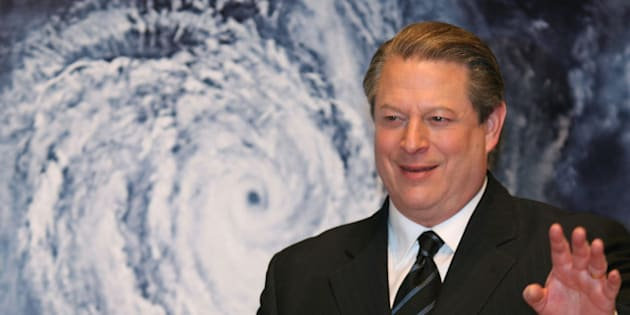 """Former Vice President Al Gore acknowledges spectators in front of a poster of his starring documentary film """"An Inconvenient Truth"""" on global warning before its screening during the Japan Premier at a Tokyo theater Monday, Jan. 15, 2007. (AP Photo/Koji Sasahara)"""