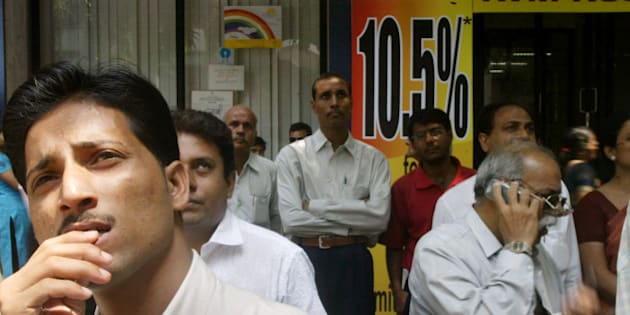 People watch a screen displaying the share prices outside the building of the Bombay Stock Exchange in Mumbai, India, Monday, April 2, 2007. Indian shares fell sharply in early trade Monday, spooked by fresh moves from the country's central bank to tighten monetary policy and increase lending rates that could likely slow economic growth. The 30-share Sensex of the Bombay Stock Exchange plunged 394 points, 3 percent, to 12,678 points in early trading. On the broader National Stock Exchange, the 50-company S&P Nifty index fell 3.2 percent to 3,700 points. (AP Photo/Gautam Singh)