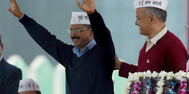 Aam Aadmi Party (AAP) president Arvind Kejriwal (L) greets his supporters as fellow Minister Manish Sisodia (R) congratulates him during his swearing-in ceremony as Delhi chief minister in New Delhi on February 14, 2015.  Arvind Kejriwal promised to make Delhi India's first corruption-free state and end what he called its 'VIP culture' as he was sworn in as chief minister before a huge crowd of cheering supporters .   AFP PHOTO / PRAKASH SINGH        (Photo credit should read PRAKASH SINGH/AFP/Getty Images)