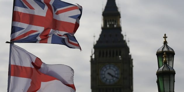 The Union, top, and England flags fly over a souvenir shop on Westminster Bridge in London, Thursday, April 2, 2015, with the Elizabeth Tower, containing the famous Big Ben in the background. Britain's political leaders are going head to head Thursday evening in a seven-way TV debate before a May 7 national election. At right is the top of a street light. (AP Photo/Tim Ireland)