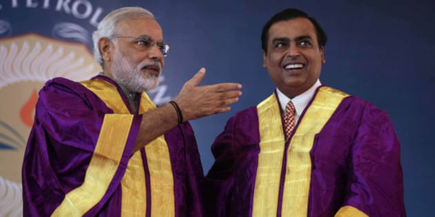 Gujarat state Chief Minister Narendra Modi, left, gestures towards Chairman and Managing Director of Reliance Industries Limited Mukesh Ambani during the convocation ceremony of Pandit Deendayal Petroleum University (PDPU) in Gandhinagar, in the western Indian state of Gujarat, Saturday, Oct. 19, 2013. Modi is India's main opposition Bharatiya Janata Party's candidate for prime minister if it wins national elections next year. (AP Photo/Ajit Solanki)