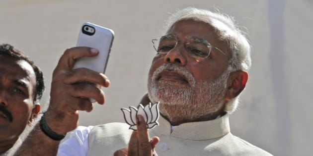 FILE- In this April 30, 2014 file photograph, India's main opposition Bharatiya Janata Party's prime ministerial candidate Narendra Modi holds his party's symbol and looks into his phone after casting his vote in Ahmadabad, India. In the Twitterverse ruled by President Barack Obama, India's new Prime Minister Modi may soon overtake the White House on Twitter.An analysis of Twitter accounts — showing the emphasis some governments put on digital diplomacy as a 21st-century tool for statecraft — projects Modi, already the fifth most-followed world leader on Twitter with 4.95 million followers, will soon overtake the White House's 4.97 million.(AP Photo/Ajit Solanki, file)
