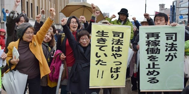 Anti nuclear activists raise their fists in the air to celebrate as the Fukui district court issued a landmark injunction against the restarting of two atomic reactors of Kansai Electric Power Co's Takahama nuclear power plant in Fukui on April 14, 2015, after the country's nuclear watchdog had given the green light to switch them back on. The Fukui district court made the temporary order in response to a bid by local residents to halt the restart of the No. 3 and No. 4 reactors at the Takahama nuclear power plant.    AFP PHOTO / JIJI PRESS    JAPAN OUT        (Photo credit should read JIJI PRESS/AFP/Getty Images)