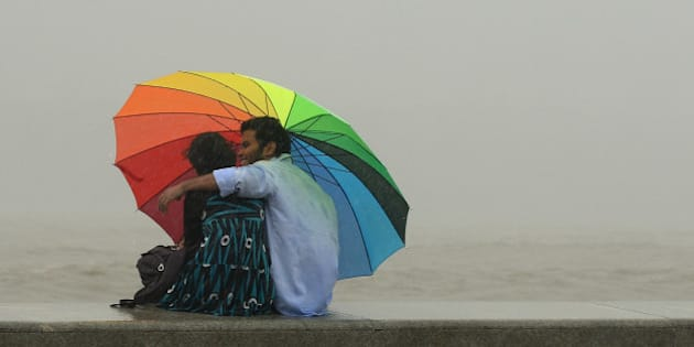 An Indian couple sit together under an umbrella during heavy rain showers at the sea front in Mumbai on July 12, 2013. The monsoon season, which runs from June to September, accounts for about 80 percent of India's annual rainfall, vital for a farm economy which lacks adequate irrigation facilities. AFP PHOTO/ PUNIT PARANJPE        (Photo credit should read PUNIT PARANJPE/AFP/Getty Images)