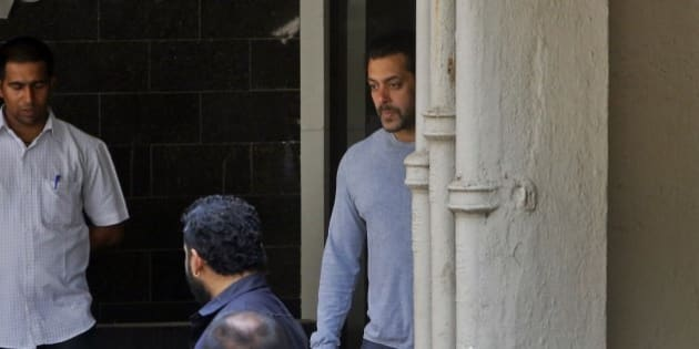 Bollywood actor Salman Khan, center, comes out of his residence to see off a guest in Mumbai, India, Thursday, May 7, 2015. One of India's biggest and most popular movie stars, Khan, was sentenced to five years in jail Wednesday on charges of driving a vehicle over five men sleeping on a sidewalk and killing one in a hit-and-run case that has dragged for more than 12 years. (AP Photo/Rajanish Kakade)