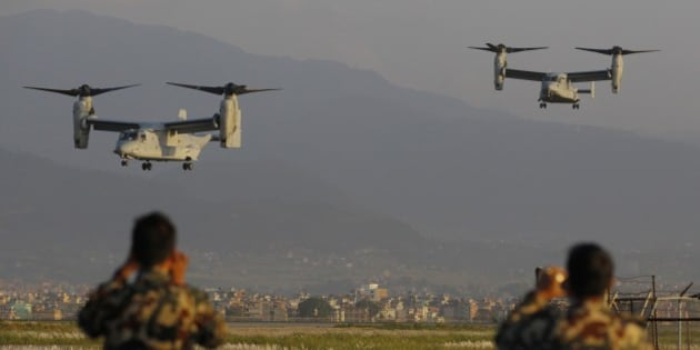 Nepalese soldiers take pictures as US Air Force Bell Boeing V-22 Osprey aircrafts arrive at the Tribhuvan International airport in Kathmandu, Nepal, Sunday, May 3, 2015. Runway damage forced Nepalese authorities to close the main airport Sunday to large aircraft delivering aid to millions of people following the massive earthquake, but U.N. officials said the overall logistics situation was improving. Airport congestion was only the latest complication in global efforts to aid people in the wake of the April 25 quake, the impoverished country's biggest and most destructive in eight decades. (AP Photo/Niranjan Shrestha)