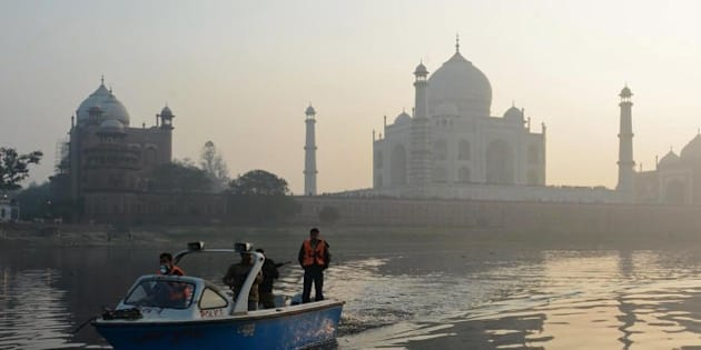 The historic Taj Mahal monument is pictured as a police patrol boat moves over the Yamuna river in Agra on January 18, 2015. Known as a 'monument to love' the Taj Mahal is a mausoleum built by Mughal Emperor Shah Jahan in memory of his favorite wife, Mumtaz Mahal. Construction of the Taj Mahal began around 1632, was completed around 1653 and is considered one of the finest examples of Mughal architecture - a style which combines Indian, Islamic and Persian elements. AFP PHOTO/STR        (Photo credit should read STRDEL/AFP/Getty Images)