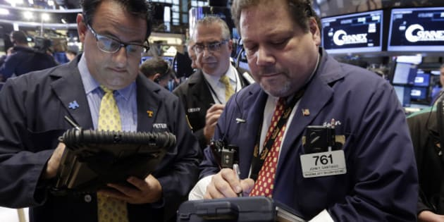 Traders Peter Costa, Kenneth Polcari, and John Santiago, left to right, work on the floor of the New York Stock Exchange Thursday, May 7, 2015. U.S. stocks are opening mostly lower, pushing the Dow Jones industrial average into the red for the year. (AP Photo/Richard Drew)