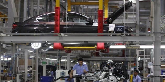 India's retired cricket star Sachin Tendulkar, center, fixes a gear shift to an engine as he assembles a BMW 5 Series at BMW's manufacturing facility on the outskirts of Chennai, India, Thursday, May 7, 2015. Tendulkar assembled the series to mark the German luxury carmaker increasing its level of local content in cars assembled in the plant by fifty percent, a company press release said. (AP Photo/Arun Sankar K)
