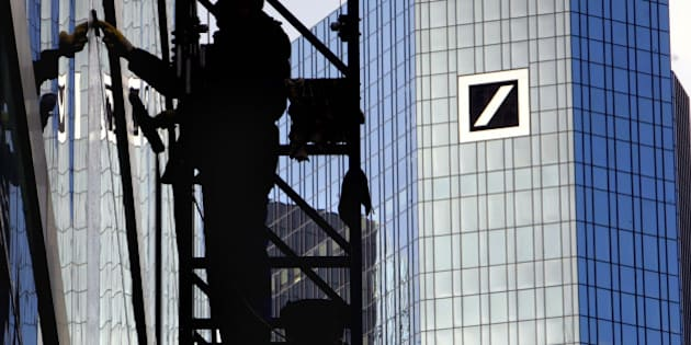 "** FILE ** A window cleaner cleans a building next to the Deutsche Bank, right, in Frankfurt, central Germany, in this Feb. 1., 2007 file photo. Deutsche Bank says persistent difficult conditions in global financial markets could hurt its 2008 target pretax profit of euro 8.4 billion (US$13.1 billion). Deutsche Bank said in its annual report released Wednesday, March 26, 2008 that ""continuing difficult market conditions may require us to write down the carrying values of some of our portfolios of assets, including leveraged loans and loan commitments.""  (AP Photo/Michael Probst)"