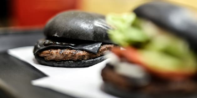 TOKYO, JAPAN - SEPTEMBER 18:  Black hamburgers are seen at a Burger King restaurant on September 18, 2014 in Tokyo, Japan. The black burgers, one a Kuro Pearl at 480 yen, has black buns and cheese smoked with bamboo charcoal and black sauce made of squid ink. The other, the Kuro Diamond at 690 yen, comes also with lettuce, tomato, onion and mayonnaise. The burgers are available from September 19 through early November in Burger King restaurants throughout Japan.  (Photo by Keith Tsuji/Getty Images)