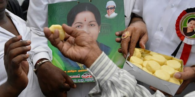 Supporters of All India Anna Dravida Munnetra Kazhagam (AIADMK) supremo, Jayalalithaa Jayaram distribute sweets as they hear the news of the acquital of their leader in the 18-year-old, disproportionate assets case in Bangalore on May 11, 2015.  The head of India's largest Tamil party was cleared of corruption May 11, 2015, a verdict that sparked wild celebrations by supporters and paved the way for the return of one of the country's most powerful politicians.     AFP PHOTO/ Manjunath KIRAN        (Photo credit should read Manjunath Kiran/AFP/Getty Images)