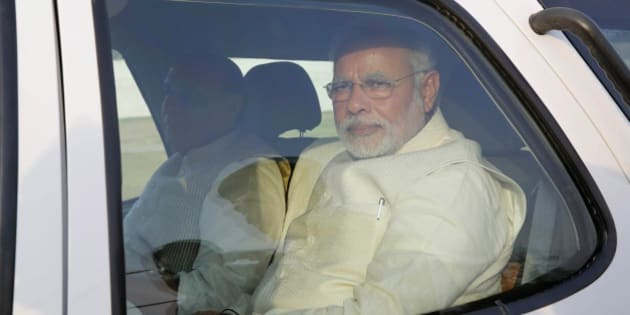 Hindu nationalist Bharatiya Janata Party leader and India's next prime minister Narendra Modi sits inside a car after his arrival in Varanasi, an ancient city revered by millions of devout Hindus, India, Saturday, May 17, 2014. Modi will be India's next prime minister, winning the most decisive victory the country has seen in more than a quarter century and sweeping the long-dominant Congress party from power, results showed Friday. An elaborately decorated platform was built for him to offer prayers on the banks of the River Ganges in Varanasi. Saffron flags fluttered above the flower bedecked platform and thousands of supporters and onlookers milled around to watch as Hindu priests chanted sacred verses and burnt incense. (AP Photo/Rajesh Kumar Singh)