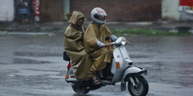 Indian policemen ride on a scooter during a curfew even as it rains in Jammu, India, Wednesday, Aug.14, 2013. Curfew continued in some parts of the Indian portion of Kashmir on Wednesday following clashes between Hindus and Muslims during the Eid holiday celebrations that claimed three lives. (AP Photo/Channi Anand)