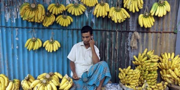 A Bangladeshi banana vendor talks on his mobile phone in Dhaka, Bangladesh, Monday, June 10, 2013. (AP Photo/A.M.Ahad)