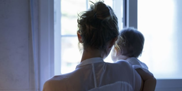 Rear view of mid adult woman and baby daughter looking out of living room window
