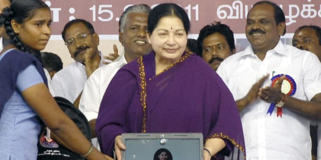 Leader of All India Anna Dravida Munnetra Kazhagam (AIADMK) party and Chief Minister of the southern Indian state of Tamil Nadu J. Jayalalithaa (C) presents a laptop computer to a student (L) during a ceremony in Chennai on September 15, 2011. The southern Indian state of Tamil Nadu on September 15 began a 2 billion USD giveaway of free laptops to every student in state-run schools and colleges over the next five years. AFP PHOTO/STR (Photo credit should read STRDEL/AFP/Getty Images)