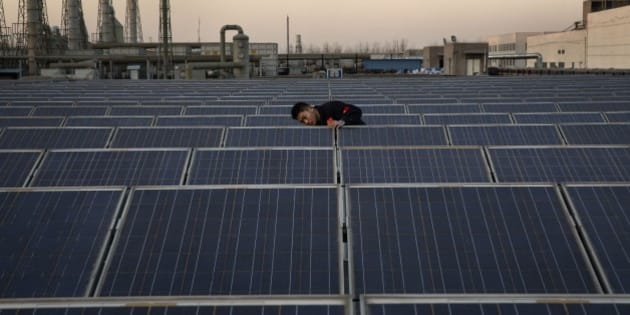 BAODING, CHINA - DECEMBER 4: A technician from Yingli Solar checks a solar panel used to produce energy for lighting, on the roof at the company's headquarters on December 4, 2014 in Baoding, Hebei Province. China is the largest energy consumer in the world with the main source of its electricity generated by coal, but in moves to reduce carbon emissions China is also setting records for installing solar panels and generating solar power. (Photo by Kevin Frayer/Getty Images)