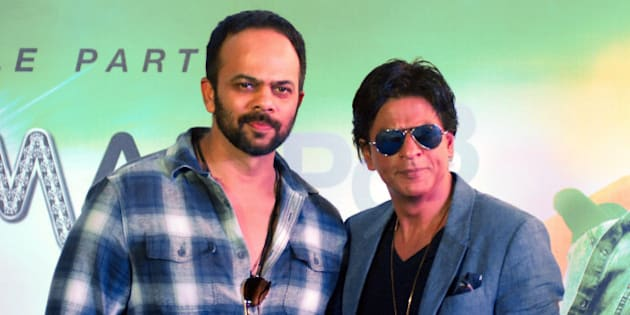 Indian Bollywood actor Shah Rukh Khan (R) poses during a promotional event for the forthcoming Hindi film Chennai Express directed by Rohit Shetty (L) in Mumbai on August 8, 2013.AFP PHOTO/STR        (Photo credit should read STRDEL/AFP/Getty Images)