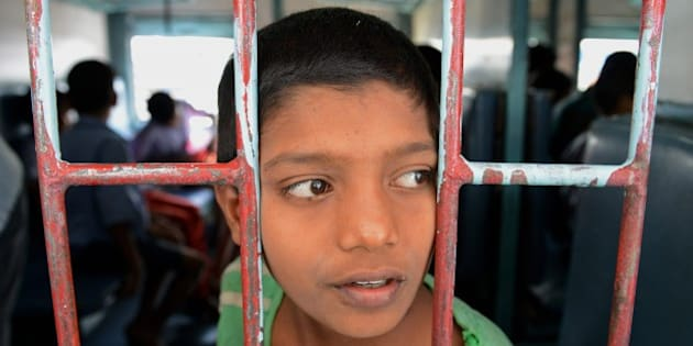 A rescued Indian child labourer looks on on board a Patna-bound express train at a railway station in Secunderabad on February 5, 2015. The children, rescued from bangle-making factories and other workshops in Secunderabad's twin city Hyderabad in the past ten days, are being sent back to their places of origin. Some 400 children hailing from India's Bihar, Uttar Pradesh and West Bengal states were rescued during raids conducted by the city police and labour department officials in different parts of the old city. AFP PHOTO / NOAH SEELAM        (Photo credit should read NOAH SEELAM/AFP/Getty Images)