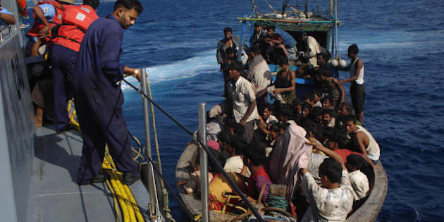 Members of the Indian coastguard rescue illegal Bangladeshi migrants in their trawler after they were sighted by the Coast Guard Aircraft off Chidiyatapu Island in the southern Andaman Islands on January 8, 2009.  The Indian Coast Guard said Sunday it had rescued hundreds of migrants from Bangladesh and Myanmar who claimed to have been arrested by Thai authorities and set adrift on the high seas. AFP PHOTO/ STR (Photo credit should read STR/AFP/Getty Images)