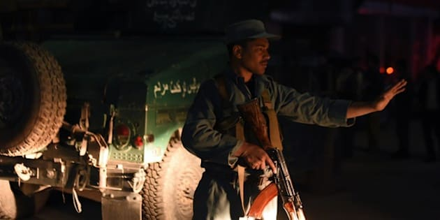 An Afghan policeman blocks a road near the Park Place guesthouse in Kabul on May 13, 2015 after gunmen stormed the place ahead of a planned concert, Afghan officials said, with people believed trapped inside and several casualties feared.. No group immediately claimed responsibility for the attack on the Park Place guesthouse in downtown Kabul, but the assault comes as the Taliban -- who have attacked such guesthouses in the past -- press their annual spring offensive. AFP PHOTO / SHAH MARAI        (Photo credit should read SHAH MARAI/AFP/Getty Images)