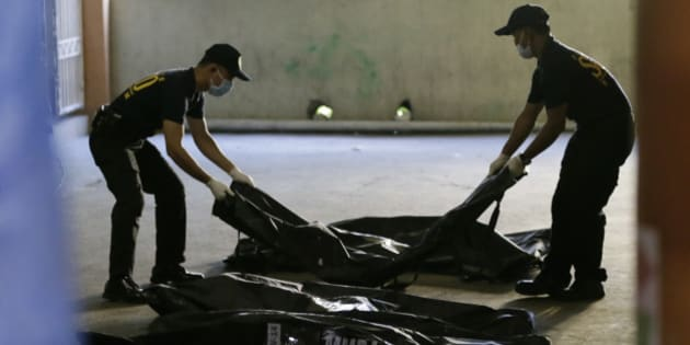 Members of Scene of the Crime Operatives of the Philippine National Police line up body bags containing the remains of victims Thursday, May 14, 2015, a day after a fire gutted Kentex rubber slipper factory in Valenzuela city, a northern suburb of Manila, Philippines. A fire gutted the factory, possibly killing dozens of workers who ran to the second floor in hopes of escaping only to become trapped by inferno, officials said. (AP Photo/Bullit Marquez)