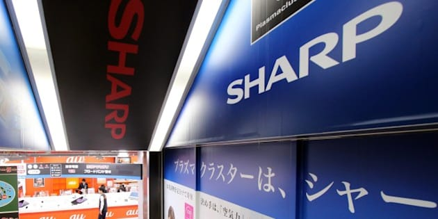Customers walk past advertisements for Japanese electronics manufacturer Sharp at an electrics shop in Tokyo on May 11, 2015. Sharp lost a quarter of its market value on May 11 following reports that the struggling Japanese electronics giant is planning a drastic capital reduction to help wipe away losses.       AFP PHOTO / Yoshikazu TSUNO        (Photo credit should read YOSHIKAZU TSUNO/AFP/Getty Images)