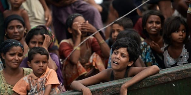 Rohingya migrants stand and sit on a boat drifting in Thai waters off the southern island of Koh Lipe in the Andaman sea on May 14, 2015.  The boat crammed with scores of Rohingya migrants -- including many young children -- was found drifting in Thai waters on May 14, according to an AFP reporter at the scene, with passengers saying several people had died over the last few days.     AFP PHOTO / Christophe ARCHAMBAULT        (Photo credit should read CHRISTOPHE ARCHAMBAULT/AFP/Getty Images)