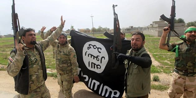 Members of the Iraqi paramilitary Popular Mobilisation units celebrate with a flag of the Islamic State (IS) group after retaking the village of Albu Ajil, near the city of Tikrit, from the jihadist group, on March 9, 2015. Some 30,000 Iraqi soldiers, police and the increasingly influential paramilitary Popular Mobilisation units, which are dominated by Shiite militias, have been involved in a week-old operation to recapture Tikrit, one of the jihadists' main hubs since they overran large parts of Iraq nine months ago.  AFP PHOTO / AHMAD AL-RUBAYE        (Photo credit should read AHMAD AL-RUBAYE/AFP/Getty Images)
